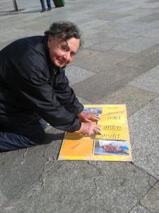 Mann zeigt auf sein plakat