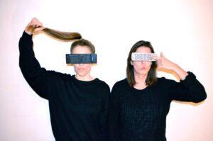 Zwei junge Frauen mit Fernbedienungen vor ihren Augen