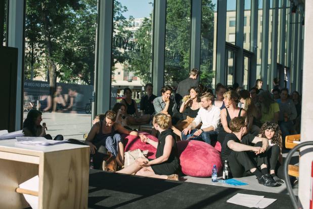 Junge Leute sitzen gemütlich auf dem Boden