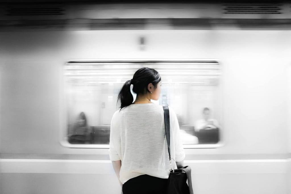 Frau steht vor einem vorbeifahrenden Zug