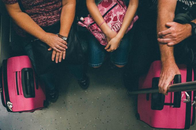 Rosa Koffer auf Zugboden