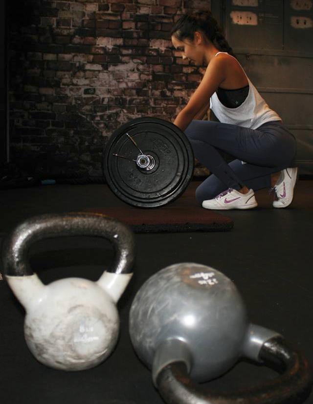 Hanteln, im Hintergrund eine Frau im Fitnesstudio
