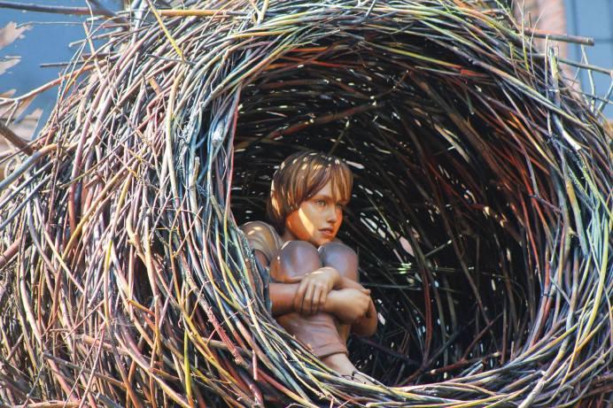 Kind sitzt in einem großen Nest