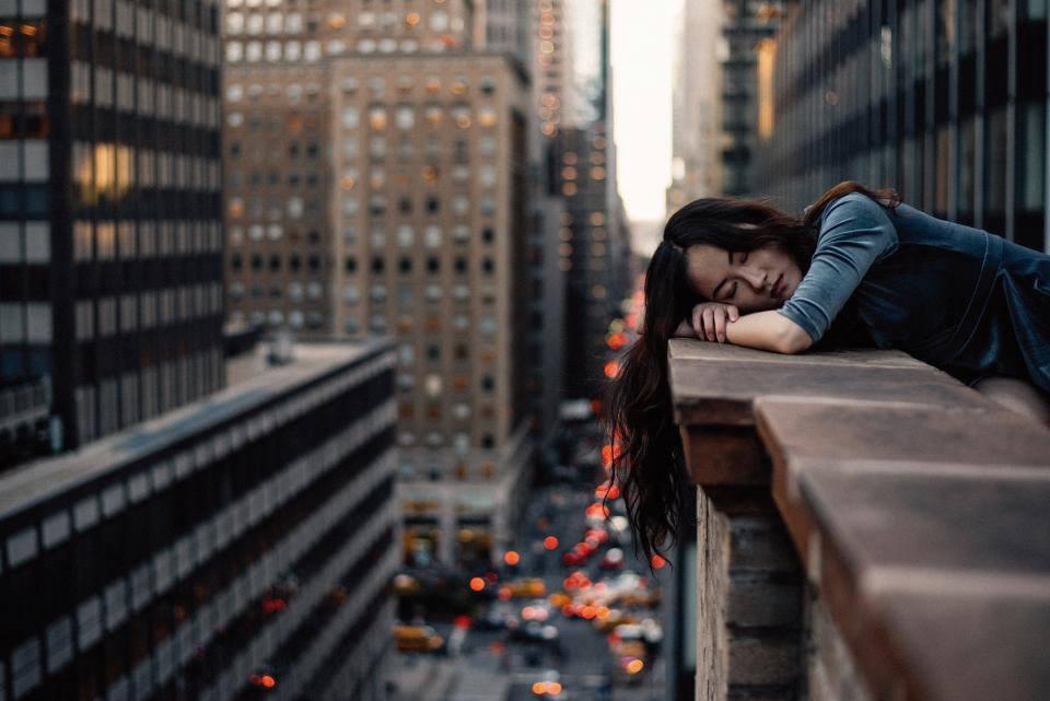 Mensch liegt auf Ballustrade eines Hauses