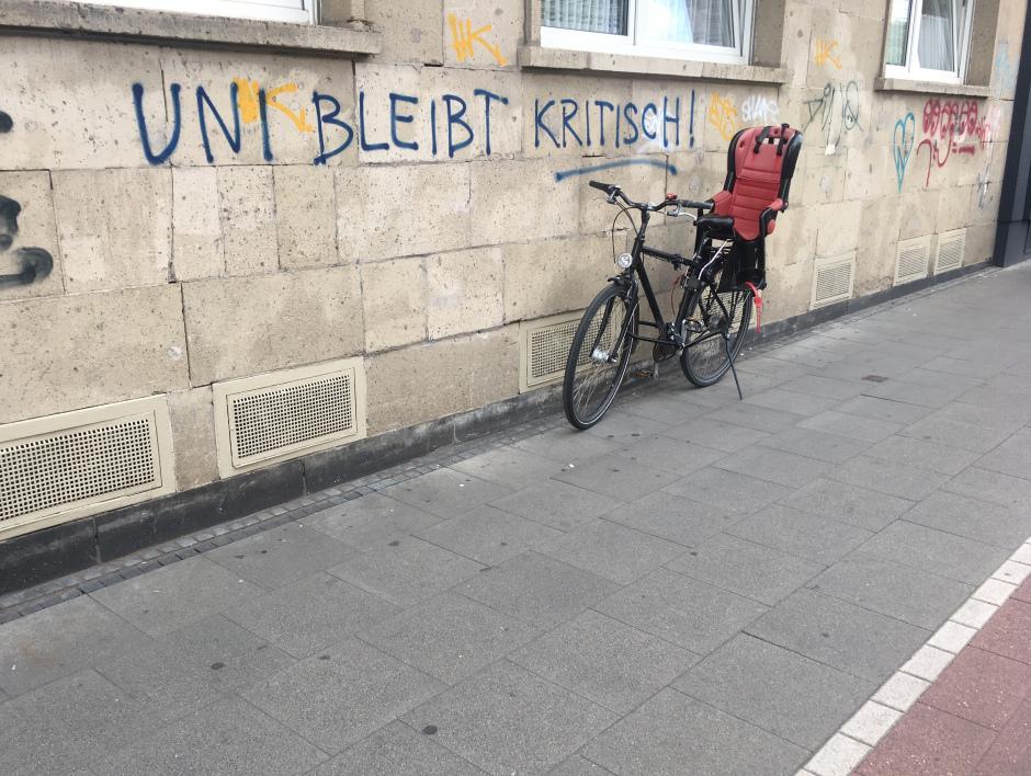 Fahrrad vor Hauswand auf dem Uni bleibt kritisch geschrieben ist