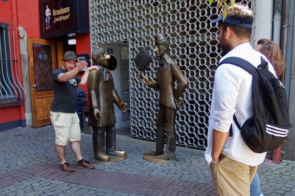 Tourguide steht vor Skulptur und erklärt