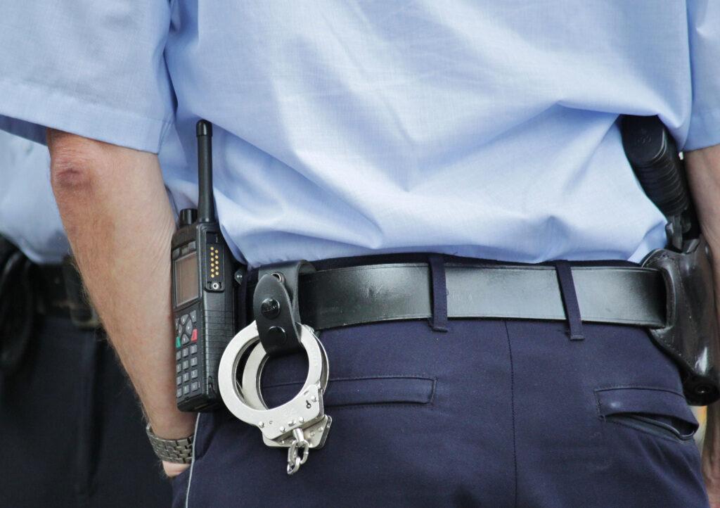 Rückansicht eines Polizisten mit Handschellen