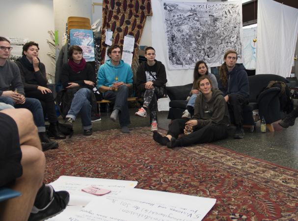 Gruppe von Studierenden sitzen auf Boden