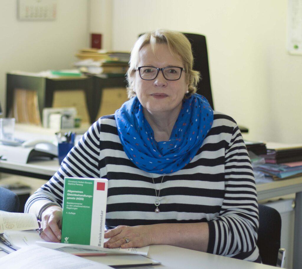 Frau sitzt am Tisch und hält Buch in der Hand