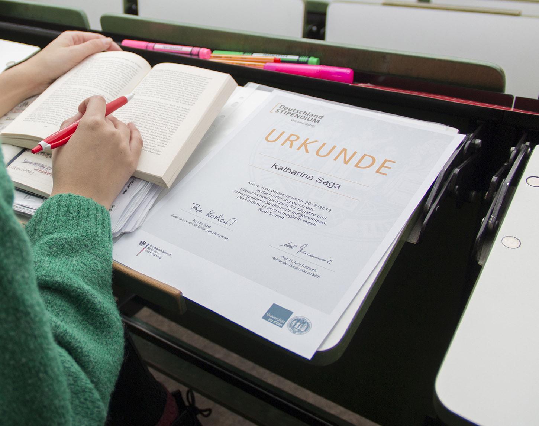 Urkunde auf Hochschulbank im Hörsaal