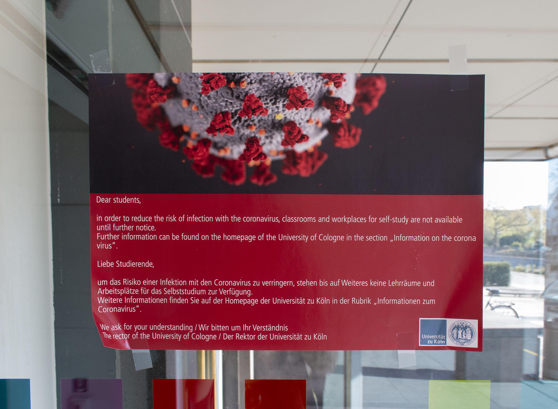 Infozettel an einer Glastür über ein Virus