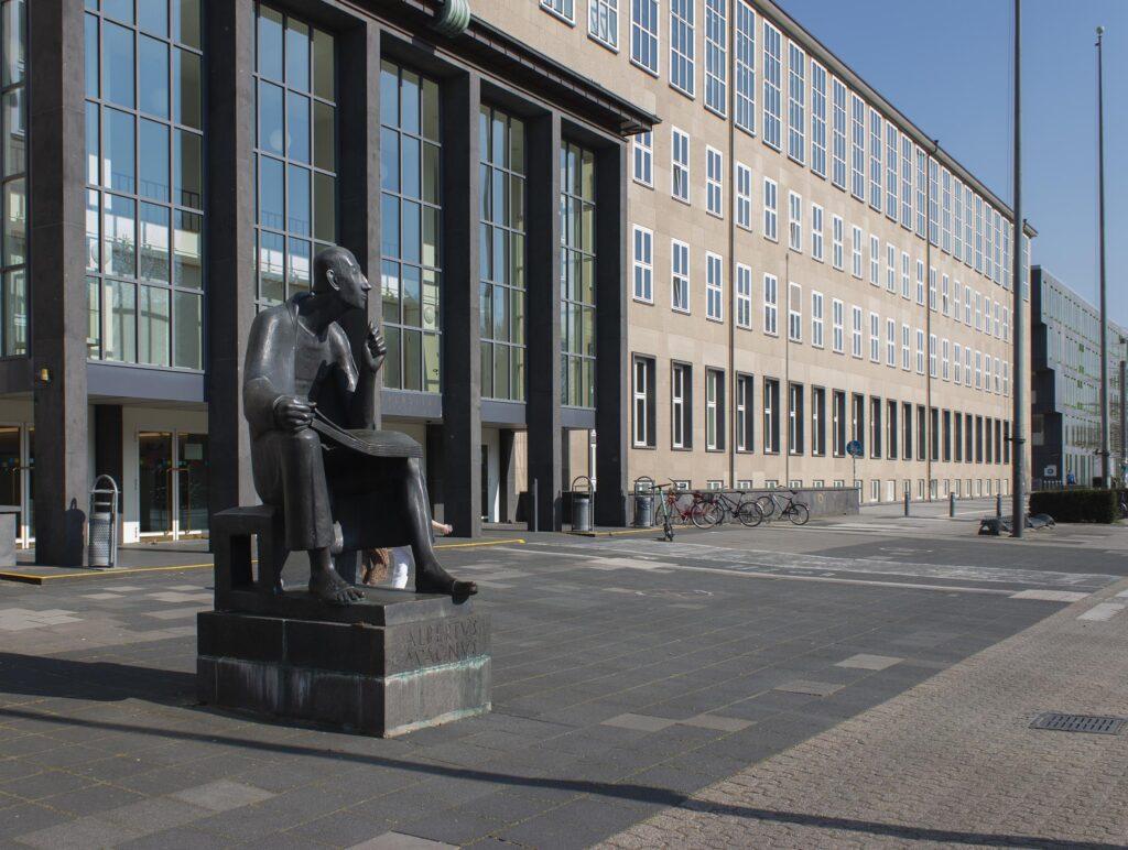 Statue mit Hauptgebäude einer Universität