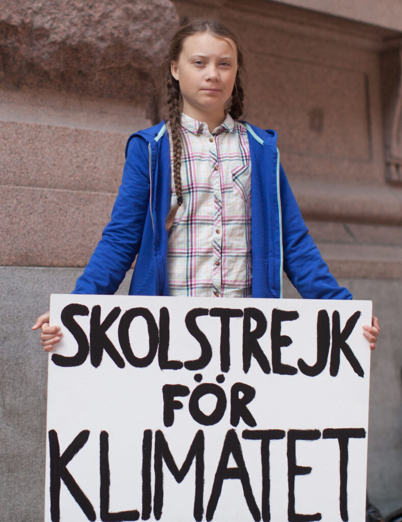 junges Mädchen hält Plakat vor sich