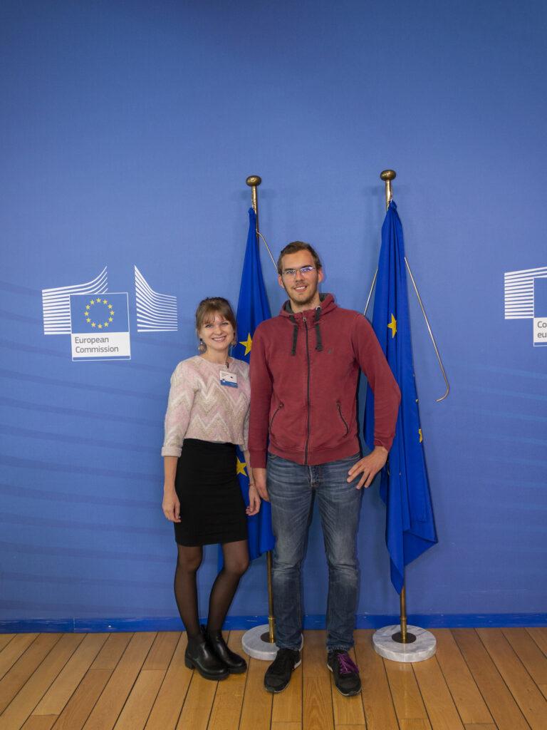 Zwei Personen vor EU-Flaggen