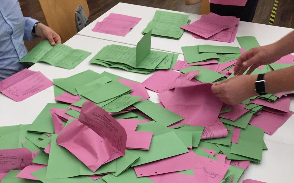 grüne und rote Wahlzettel auf weißem Tisch