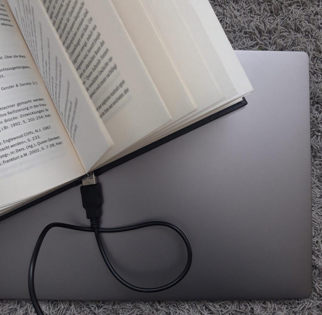 Offenes Buch an dem ein Kabel angeschlossen ist