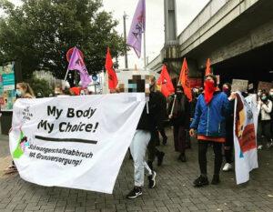 Demonstrierende gehen auf einer STraße mit einem Plakat