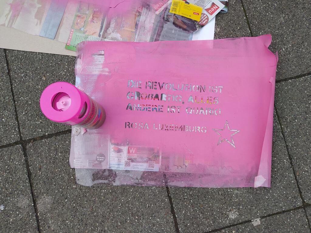 Rosa Plakat mit folgendem Zitat von Rosa Luxemburg: Die Revolution ist großartig, alles andere ist Quark!