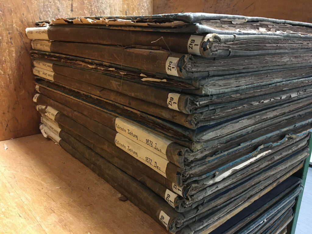 Alte kölnische Zeitungen mit Hardcover aufeinander gestalpelt.