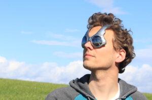 """Junger Mann auf Wiese trägt eine Sonnenbrille mit der Aufschrift """"Welcome to the Future"""" auf dem linken Glas"""