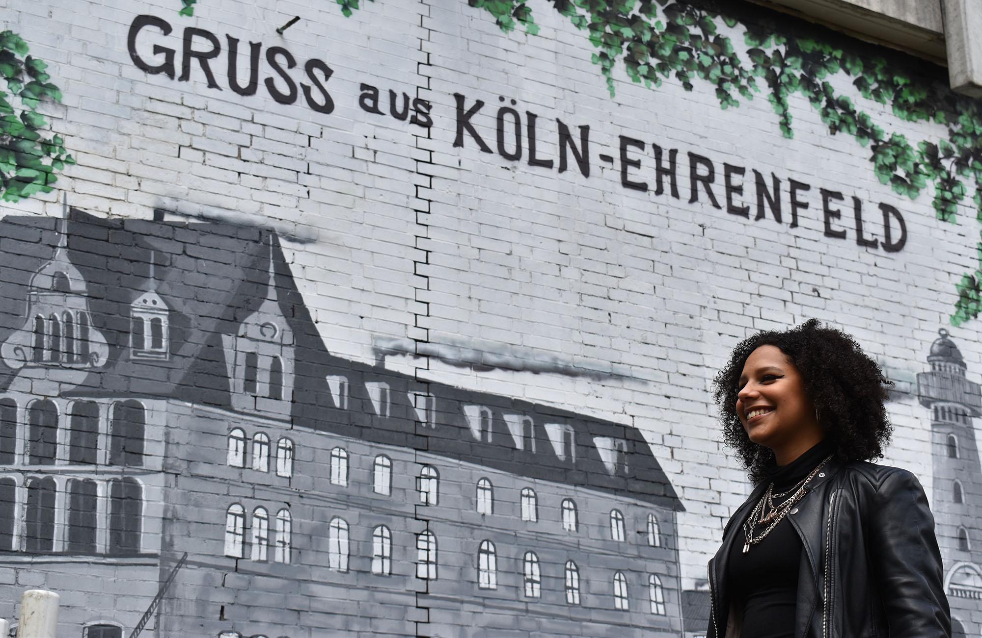 schwarze Frau vor einem Graffito
