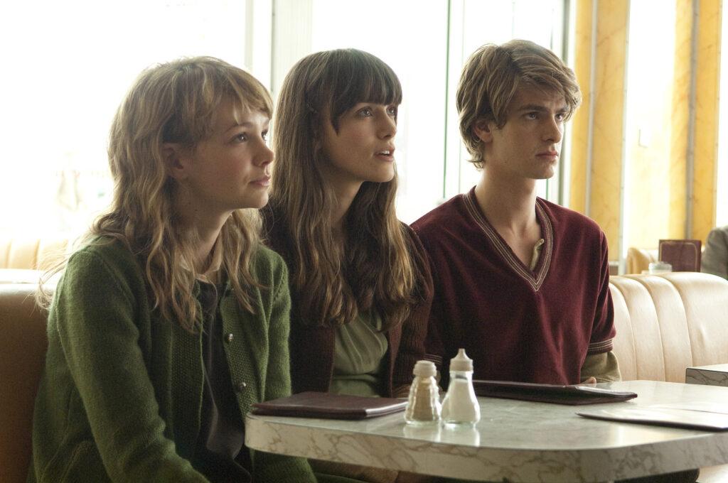 Zwei junge Frauen und ein junger Mann sitzen nebeneinander am Tisch.