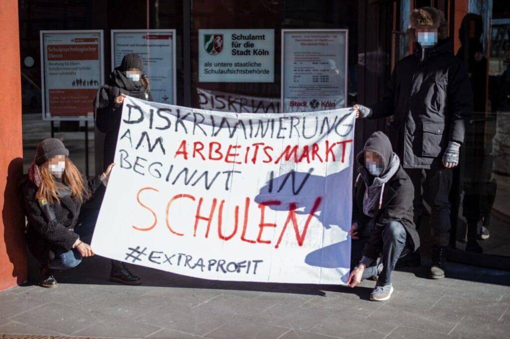 Demonstrierende halten ein Plakat gegen Diskriminierung an Schulen
