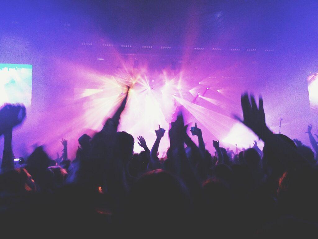 Jubelnde Menschen im Hintergrund die Konzertbühne
